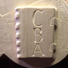 Detial of the closed book with the initials of Right Reverend Dr. Craig Barry Anderson, Eleventh Rector.