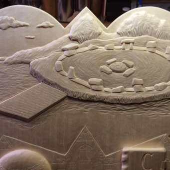 """Detail of the carving on the 2005 plaque showing the stone circle """"Stonehenge"""" project."""